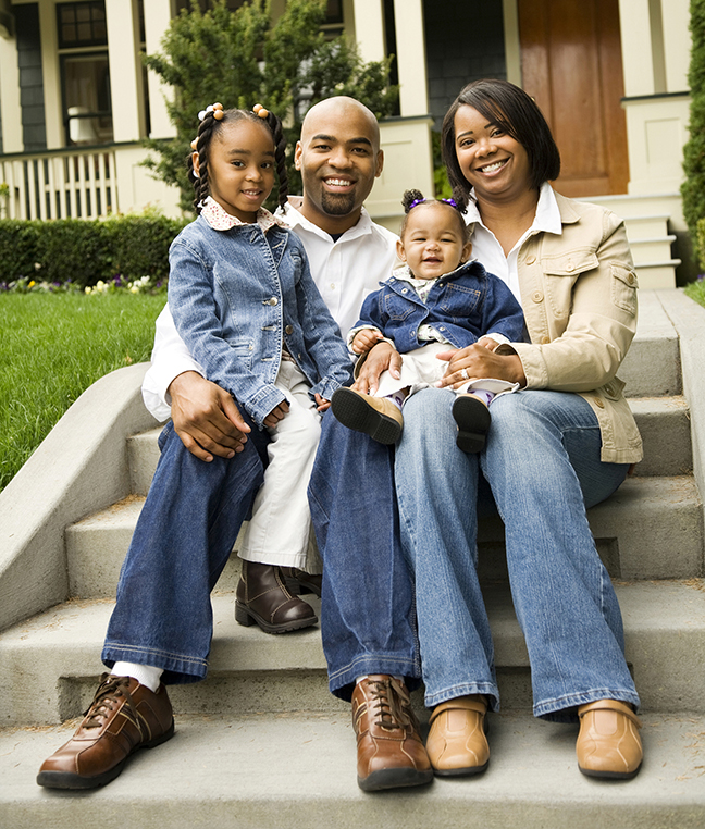 African American family smiling, sitting on front steps of house