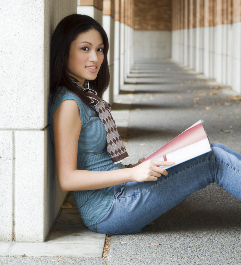 Asian female student sitting outside school and studying