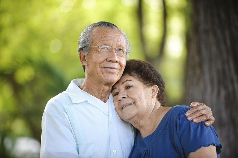 Asian older couple smling with arms around each other